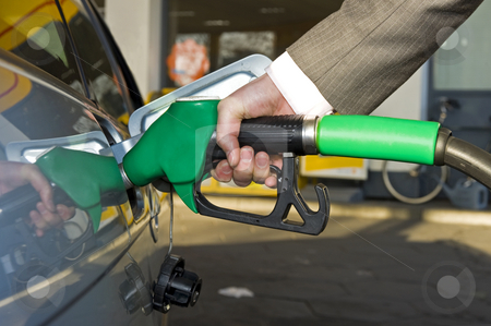 Getting gas stock photo, A man's hand filling up a car with gas or petrol at a gas station. by Corepics VOF