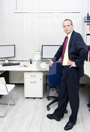 Manager in an office with blinds stock photo, Manager stading in an office in front of a desk with multiple monitors and workstations with vertical blinds by Corepics VOF