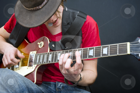 Improvising stock photo, A guitarist improvising with a plectrum in his mouth by Corepics VOF