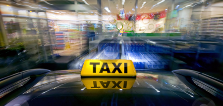 Taxi Ram Raid stock photo, A taxi at high speed closing in on a night shop for a ram raid by Corepics VOF