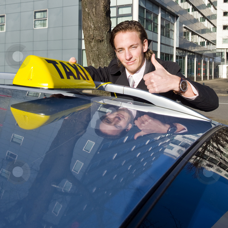 Smiling taxi driver stock photo, A smiling taxi driver giving a thumbs up while placing his taxi sign on the roof of his car by Corepics VOF