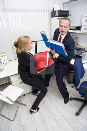 Heavy Workload stock photo, Two businesspeople scrambling to carry a heavy workload, represented by thick dossiers by Corepics VOF