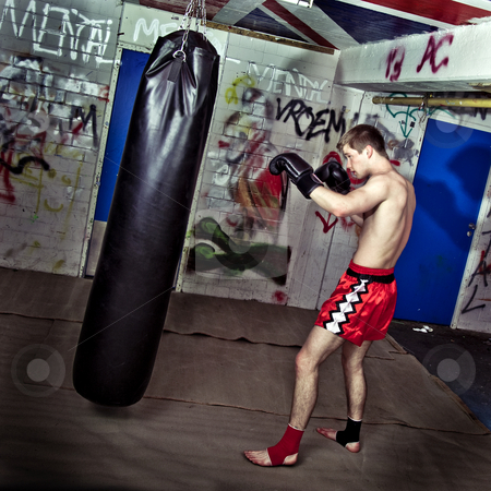 Boxing practise stock photo, Young athletic boxer training his punches and jabs on a boxing bag in a graffiti clad suburban basement by Corepics VOF