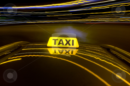 Night cab stock photo, A cab making a u-turn an urban area with the lit taxi sign on top of its roof by Corepics VOF