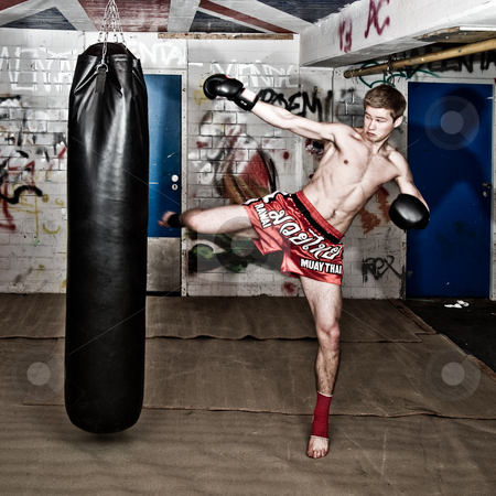 Full force kick stock photo, A muay thai fighter giving a high kick during a practise round with a boxing bag in an urban basement by Corepics VOF