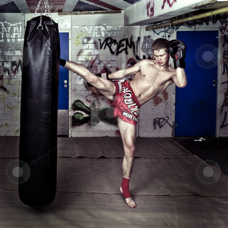 High Kick stock photo, A muay thai fighter giving a high kick during a practise round with a boxing bag in an urban basement by Corepics VOF