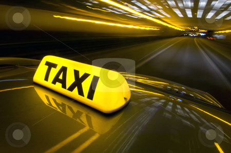 Fast taxi stock photo, A cab at high speed on a motorway in an urban area with the lit taxi sign on top of its roof by Corepics VOF