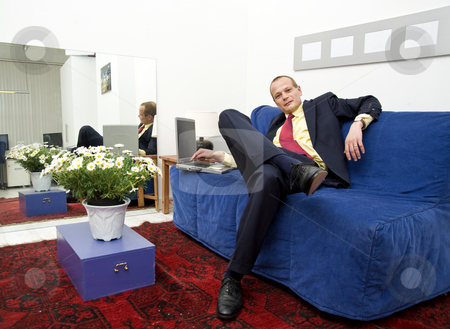 Relaxing work stock photo, Businessman at work on a comfortable couch, sitting slouched by Corepics VOF