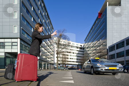 Flagging a cab stock photo, A businessman with several suitcases flagging a taxi by Corepics VOF