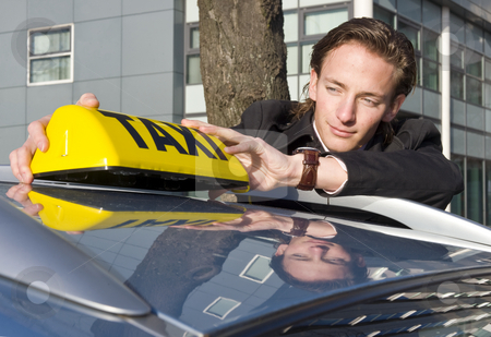 Placing the Taxi sign stock photo, A cab driver proudly placing his taxi sign on the roof of his car by Corepics VOF