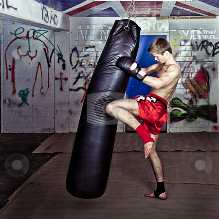 Knee kick stock photo, Athletic muay thai boxer giving a forceful knee kick during a training with a boxing bag by Corepics VOF