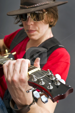 Guitarist stock photo, A guitarist getting the maximum from his guitar. Selective focus on the musicians left hand by Corepics VOF