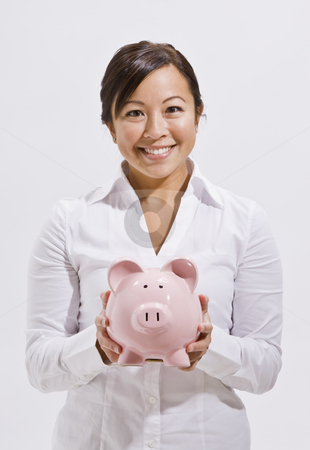 Beautiful Asian Woman Holding Piggy Bank stock photo, A beautiful and young asian woman holding a piggy bank.  She is smiling at the camera. Vertically framed shot. by Jonathan Ross