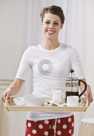 Attractive Brunette Female With Coffee on a Tray stock photo, Attractive woman serving coffee in a french press. She is smiling and looking at the camera. Vertically Framed Photo. by Jonathan Ross
