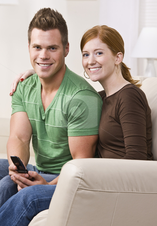 Attractive Young Couple Sitting Together on Couch stock photo, Attractive young caucasian couple sitting next to each other on a sofa and smiling. Vertically framed photo. by Jonathan Ross