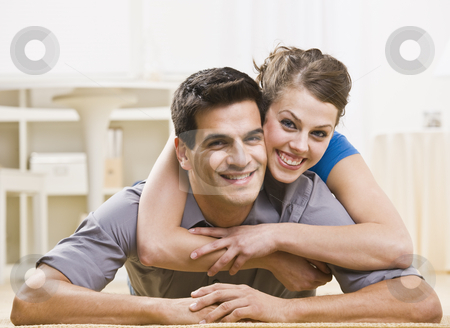 Attractive Couple Posing Together stock photo, An attractive young couple posing together. The female is on his back and has her arms around his neck affectionately. They are smiling at the camera. Horizontally framed shot. by Jonathan Ross