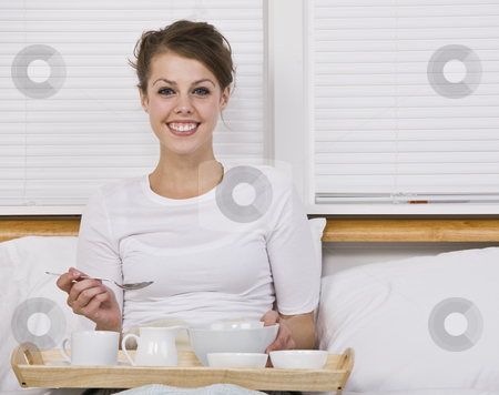Attractive Brunette with Breakfast in Bed stock photo, An attractive young woman eating breakfast in bed. She is smiling at the camera. Horizontally framed shot. by Jonathan Ross
