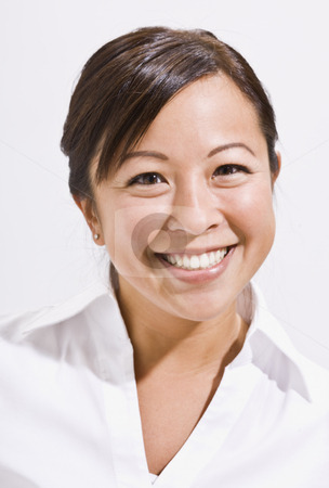 Headshot of Cute Asian Woman stock photo, A headshot of an attractive young asian woman.  She is smiling directly at the camera. Vertically framed shot. by Jonathan Ross