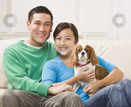 Attractive Asian Couple Holding Dog stock photo, An attractive young asian couple sitting on a couch together and holding a dog.  They are smiling at the camera.  Horizontally framed shot. by Jonathan Ross
