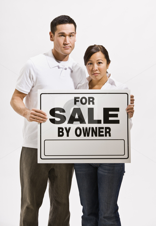 Worried Couple Holding For Sale Sign stock photo, A worried looking asian couple holding a 'For Sale' sign.  They are looking directly at the camera. Vertically framed shot. by Jonathan Ross