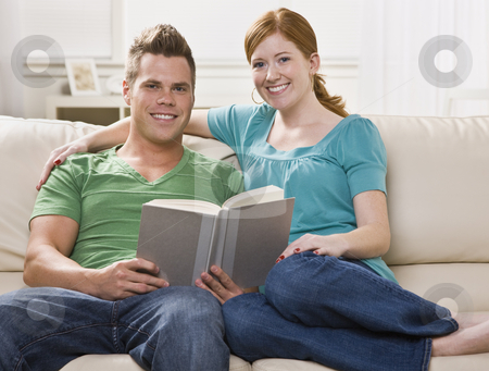 Happy Couple Reading Together stock photo, An attractive young couple reading together on a couch happily. They are smiling directly at the camera. Horizontally framed shot. by Jonathan Ross