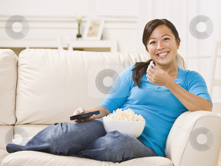 Beautiful Woman on the Couch Eating Popcorn stock photo, Beautiful Asian woman sitting on the couch eating popcorn with the remote in her hand. Horizontally framed photo. by Jonathan Ross