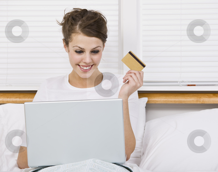 Attractive Brunette Holding Credit Card stock photo, An attractive young woman holding a credit card while using a laptop.  She is smiling at the laptop screen.  Horizontally framed shot. by Jonathan Ross