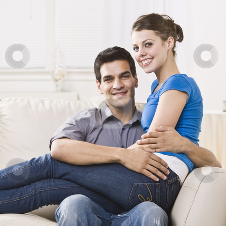 Attractive Couple Relaxing stock photo, An attractive young couple relaxing together in their home.  The woman is sitting on the man's lap and they are smiling at the camera happily. Square composition. by Jonathan Ross