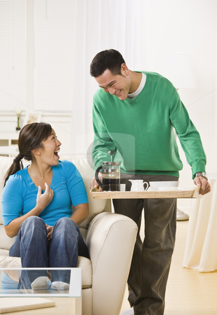 Happy Couple Having Coffee at Home stock photo, A man standing with coffee service and a woman sitting down with a surprised look on her face. Vertically framed photo. by Jonathan Ross