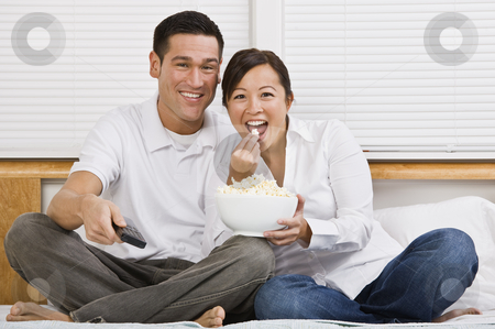 Attractive Asian Couple Eating Popcorn in Bed stock photo, Attractive asian couple sitting on a bed together and eating popcorn. Horizontally framed shot. by Jonathan Ross