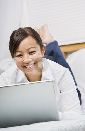 Attractive Asian Woman Lying Down with Laptop stock photo, Attractive Asian woman lying down and smiling while working on a laptop. Vertically framed photo. by Jonathan Ross