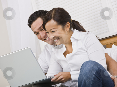 Happy Couple Sitting Together and Looking at a Laptop stock photo, Attractive asian couple smiling while looking at a laptop screen together. Horizontally framed photo. by Jonathan Ross
