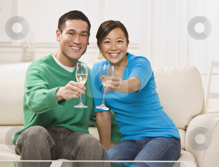 Attractive Asian Couple Toasting stock photo, An attractive young asian couple toasting champagne.  They are seated on a couch together and are smiling at the camera. Horizontally framed shot. by Jonathan Ross