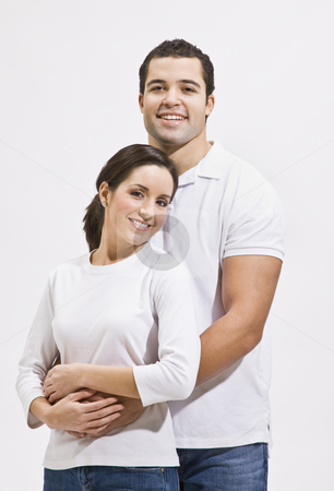 Attractive Couple Hugging and Smiling stock photo, Attractive young multi-ethnic couple standing together and hugging. Vertically framed photo. by Jonathan Ross