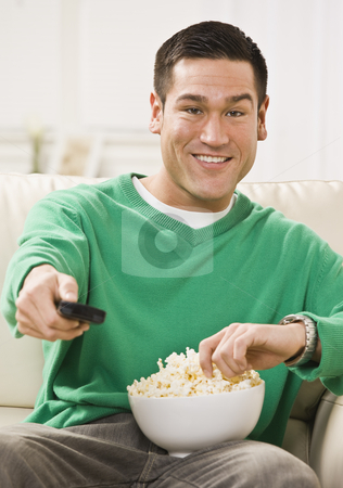 Attractive Asian Man with Popcorn and Remote Control stock photo, Attractive Asian man sitting on a sofa with popcorn and a remote control. Vertically framed photo by Jonathan Ross