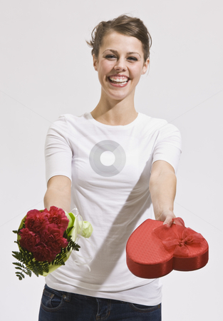 Attractive Young Woman Holding Out Roses and Candy stock photo, Smiling caucasian woman holding out Valentine's Day roses and candy while looking at the camera. Vertically framed photo. by Jonathan Ross