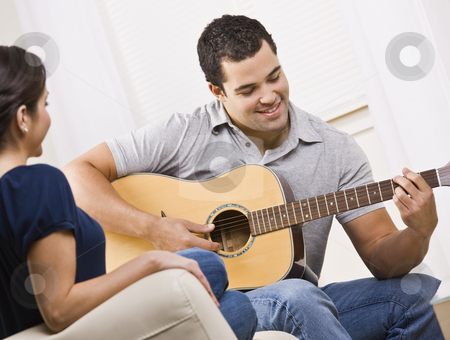 Happy Young Couple with Guitar stock photo, A young and attractive couple sitting on a couch with a guitar.  The male is playing the guitar and the female is watching.  They are smiling.  Horizontally framed shot. by Jonathan Ross