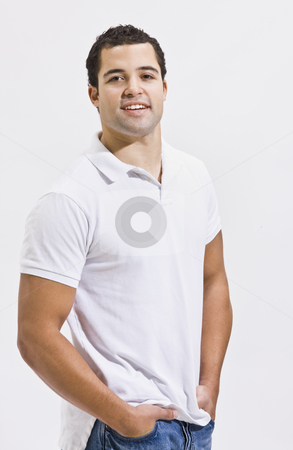 Attractive Man Posing stock photo, An attractive man posing in blue jeans and a polo shirt. He is smiling directly at the camera. Vertically framed shot. by Jonathan Ross