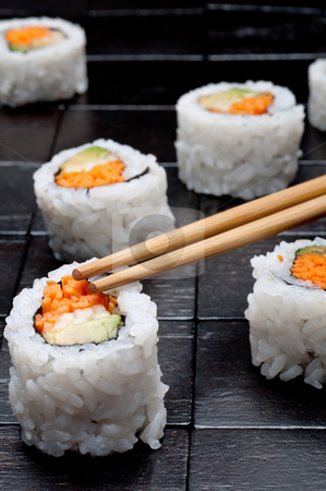 Shallow focus vertical close up of sushi with chopsticks on a bl stock photo, Shallow focus vertical close up of sushi with chopsticks on a black wooden background by Vince Clements