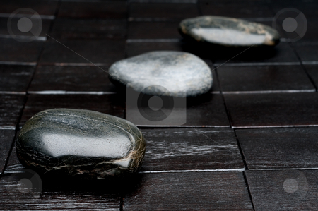 Horizontal shallow focus image of 3 river rocks on black wood stock photo, Horizontal shallow focus image of 3 river rocks on black wood by Vince Clements