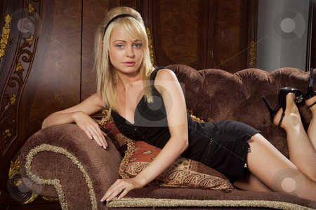 Blonde stock photo, The attractive blonde sits on a cosy sofa. by Sergey Goruppa