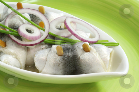Rolled herring stock photo, Rolled herring in a bowl on green background by Birgit Reitz-Hofmann