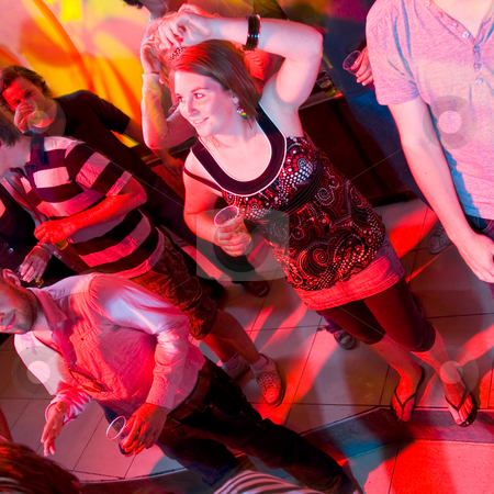 Dancing woman in a nightclub stock photo, A dancing woman in a nightclub surrounded by a group of people. by Corepics VOF