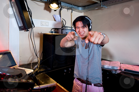 DJ in action stock photo, A Dj in a dj booth smiling and pointing at the camera by Corepics VOF
