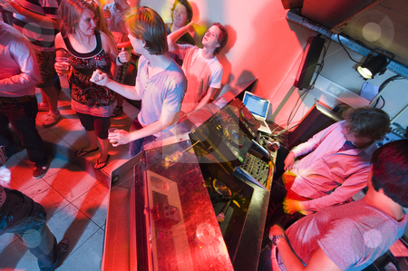 Nightclub stock photo, People dancing and flirting near the DJ booth at a nightclub by Corepics VOF