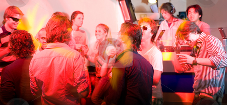 A party in a nightclub stock photo, A party on the dancefloor in a nightclub in front of the DJ booth. by Corepics VOF