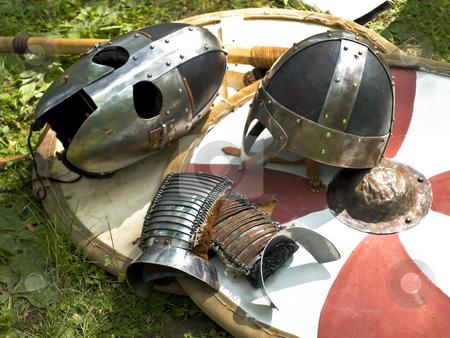 Armor stock photo, Knight metal helmets over the stripped shield by Sergej Razvodovskij