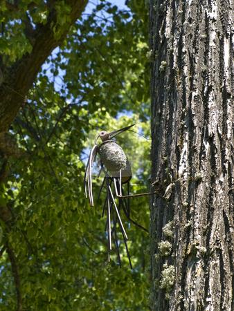 Metal woodpecker stock photo, Metal figure of woodpecker on the tree by Sergej Razvodovskij