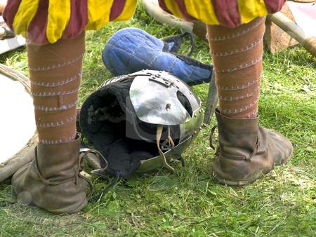Knight helmet  stock photo, Helmet on the green grass between knight legs by Sergej Razvodovskij