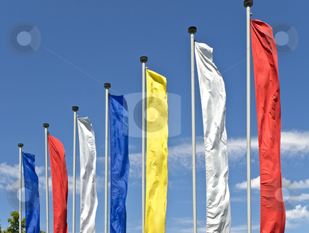 Colors stock photo, Multicolored flags against the blue cloudy sky by Sergej Razvodovskij